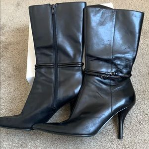 Black leather boots with straps around ankles
